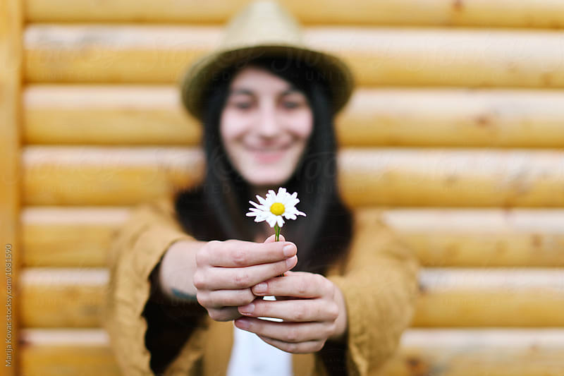 Woman holding flower by Marija Kovac for Stocksy United