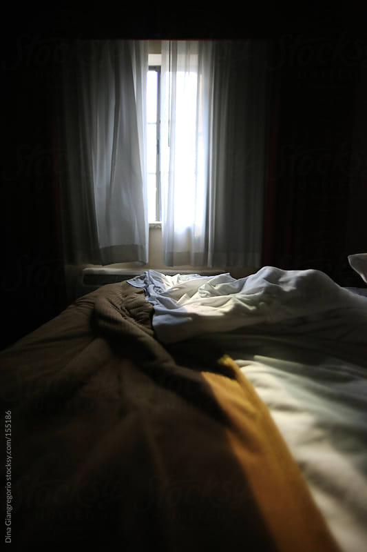 Empty hotel bed with light coming through window  by Dina Giangregorio for Stocksy United