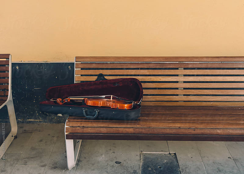 Violin in black case lying on bench by Trent Lanz for Stocksy United