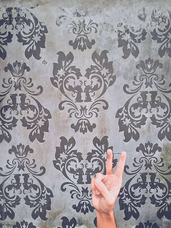 Wallpaper with peace sign with hand by Studio Firma for Stocksy United