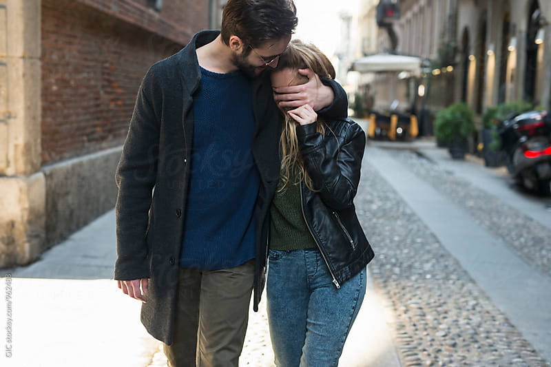 Young couple walking in the city by Simone Becchetti for Stocksy United