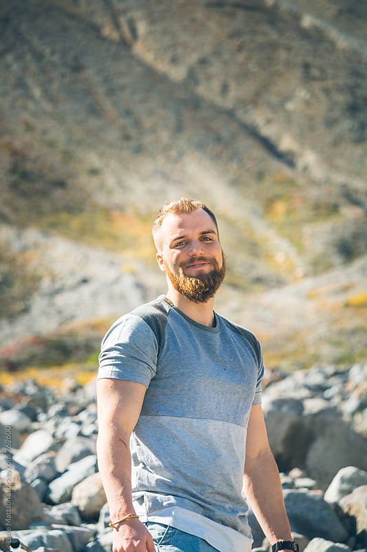 Bearded Blond Man Smiling In Rocky Riverbed While On A Hike by Luke Mattson for Stocksy United
