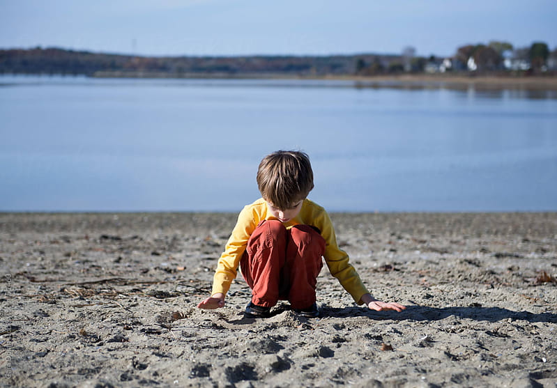 Boy sits alone on beach, reaching out to touch the sand with his palms by Cara Dolan for Stocksy United
