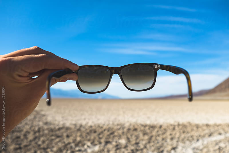 Holding sunglasses in the desert by Good Vibrations Images for Stocksy United