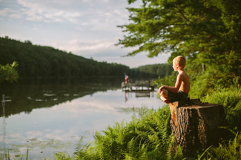 Boy Playing by Lake on Summer Vacation by Raymond Forbes LLC for Stocksy United
