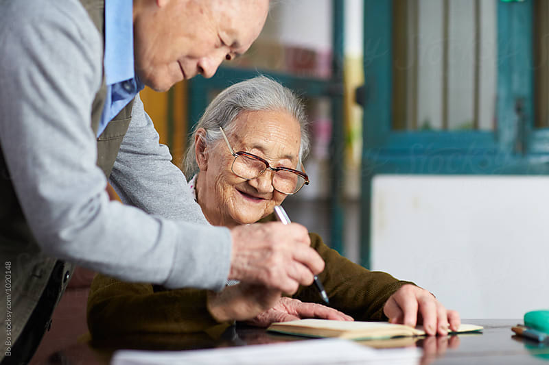senior asian couple writing by cuiyan Liu for Stocksy United
