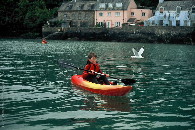 A boy sea-kayaking in Wales by Helen Rushbrook for Stocksy United