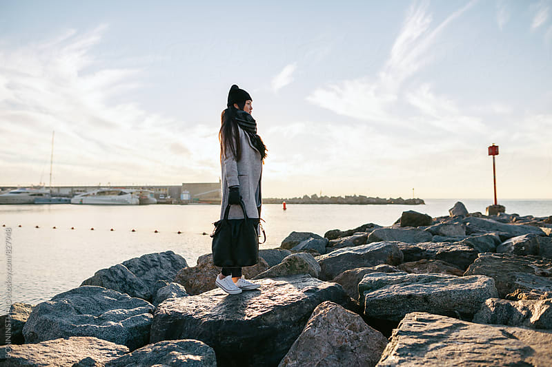 Side view of an asian woman standing on a breakwater on winter. by BONNINSTUDIO for Stocksy United