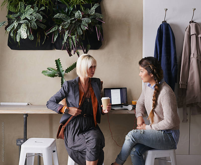 Colleagues have an informal meeting at cafe discussing business by Aila Images for Stocksy United