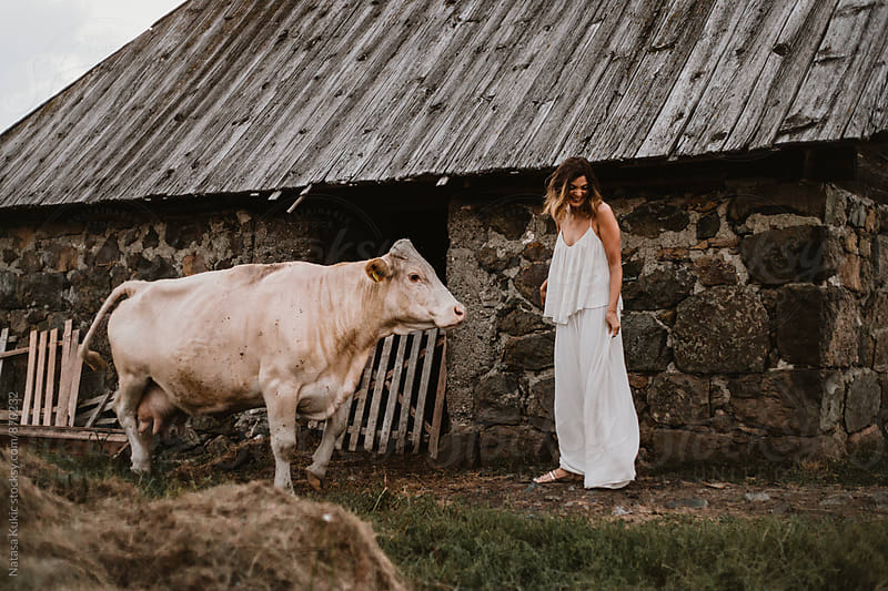 Young beautiful woman in the country and a cow by Natasa Kukic for Stocksy United