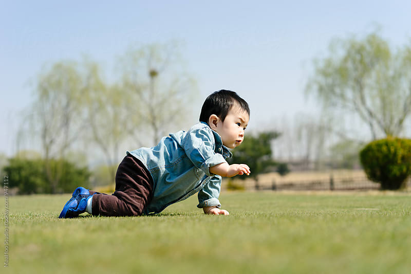 Baby boy crawling on grass in a garden by MaaHoo Studio for Stocksy United