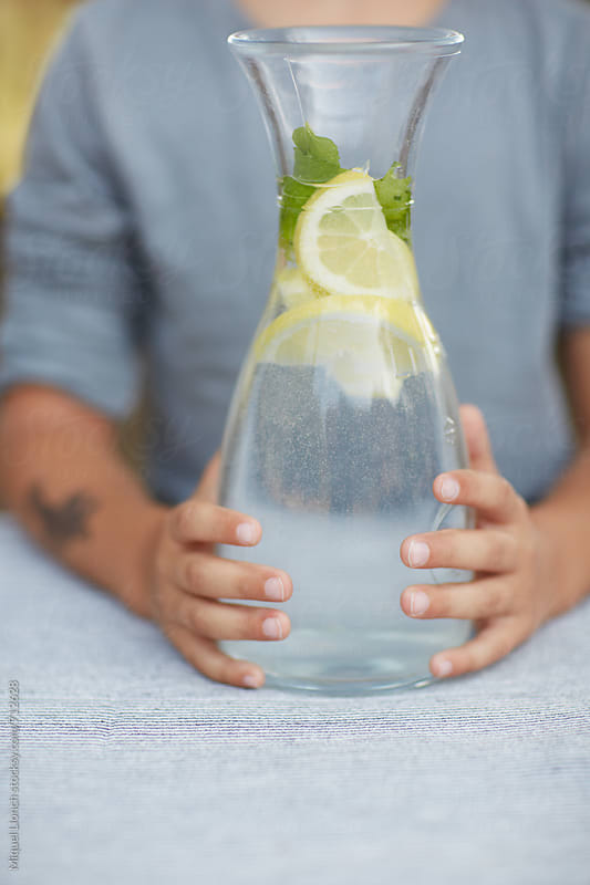 Close up of young man holding a water jar with lemon by Miquel Llonch for Stocksy United