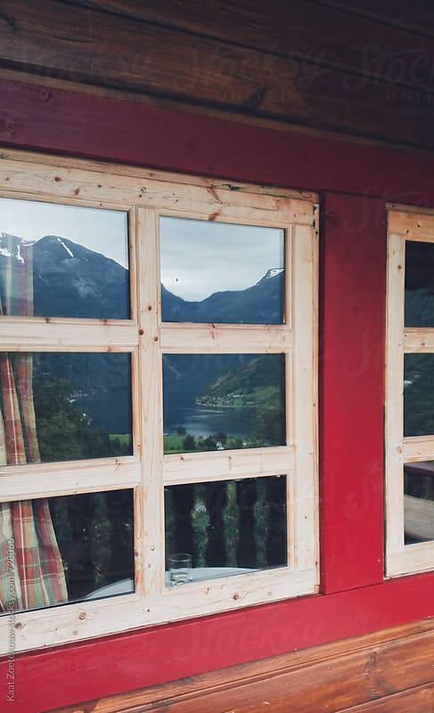 Mountain and fjord view reflected in cozy cabin window by Kaat Zoetekouw for Stocksy United