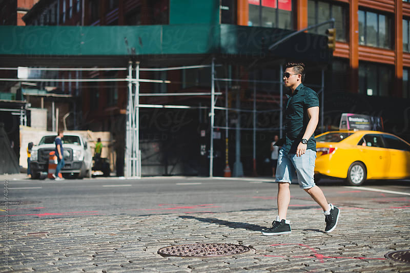 Young man walking across cobblestone street in New York City by Lauren Naefe for Stocksy United