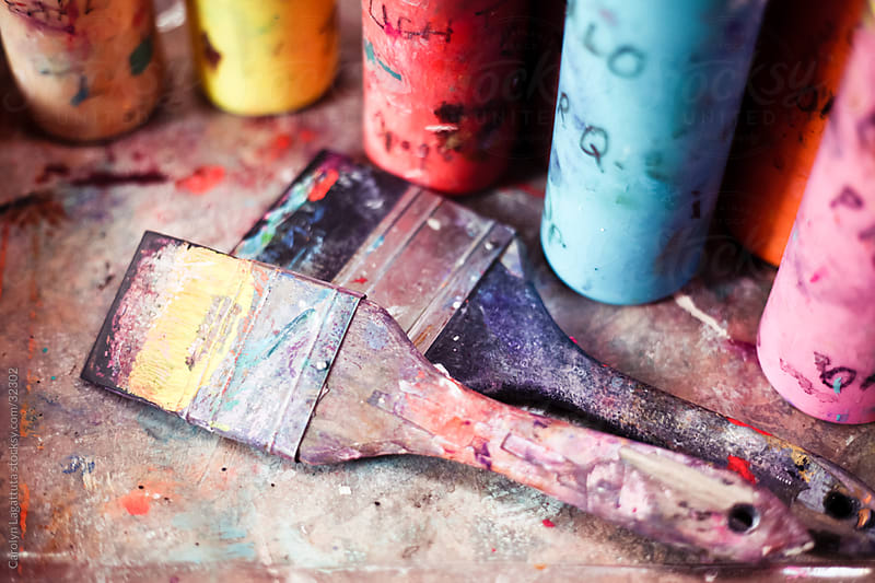 Dirty paint brushes and bottles of paint in the art studio by Carolyn Lagattuta for Stocksy United