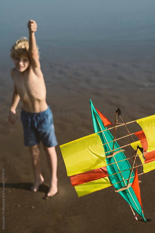 Child flying a kite at the beach by Alexander Grabchilev for Stocksy United