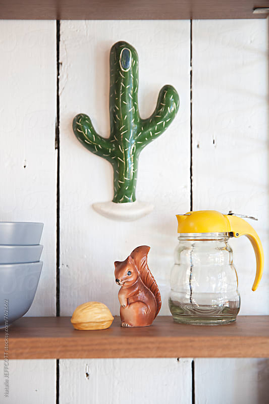 Shelves in a kitchen with fun retro items, bowls, squirrel salt and pepper shakers  by Natalie JEFFCOTT for Stocksy United