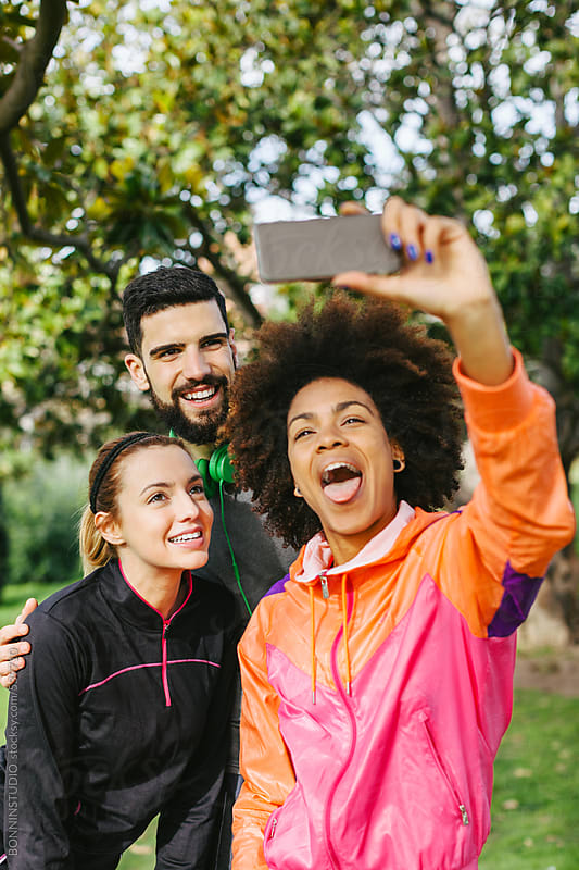 Group of young friends taking a funny selfie in the park. by BONNINSTUDIO for Stocksy United