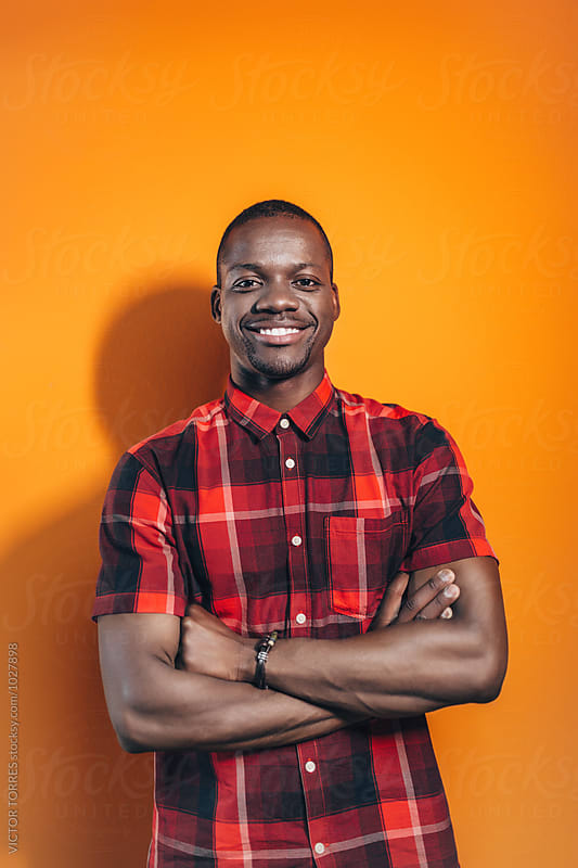 Portrait of an African Man Over an Orange Wall by VICTOR TORRES for Stocksy United