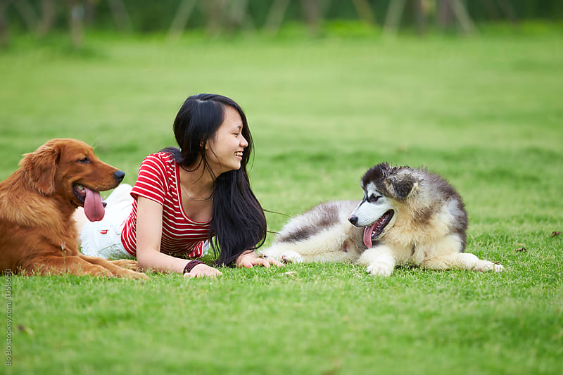 young woman lying on grass with her dog by cuiyan Liu for Stocksy United