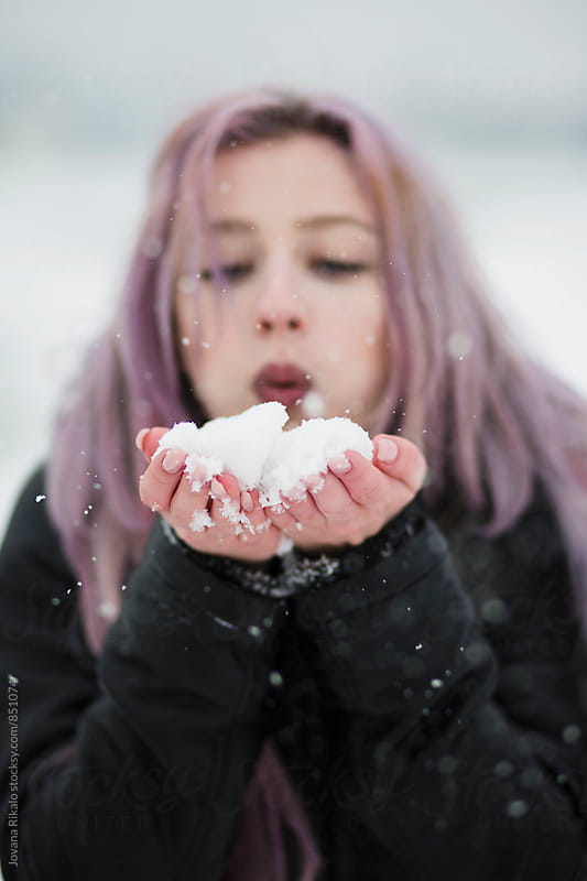 Young woman blowing handful of snow by Jovana Rikalo for Stocksy United