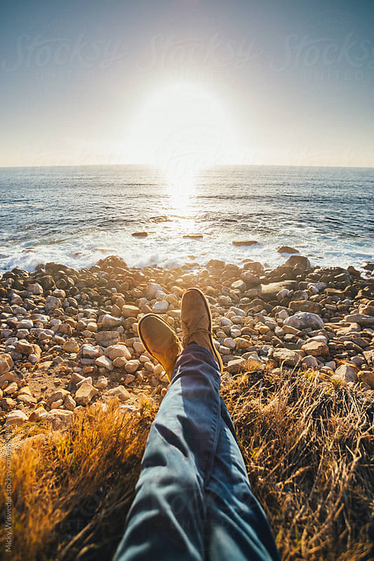 point of view of shoes and jeans overlooking a sunset on a rocky beach in summer by Micky Wiswedel for Stocksy United