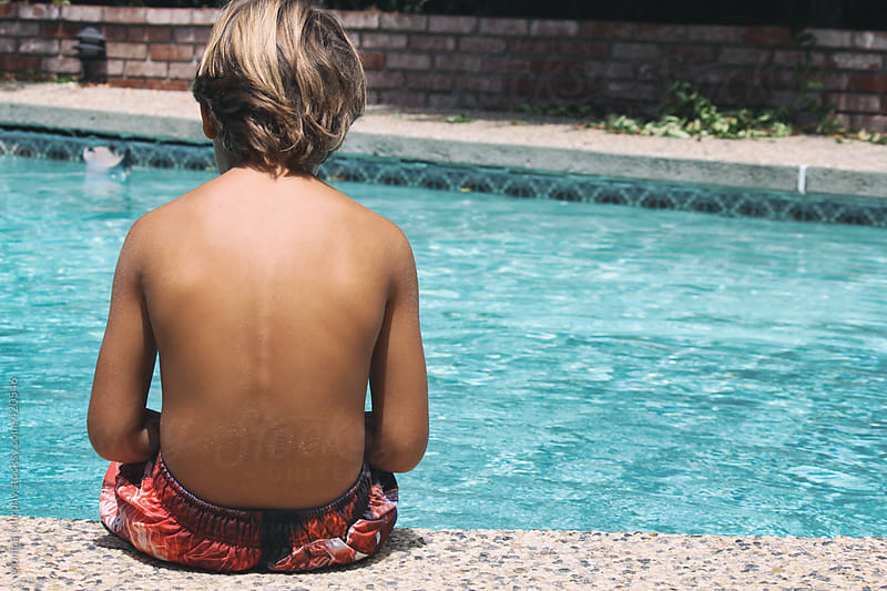 Boy sits at edge of pool, back facing camera by Monica Murphy for Stocksy United