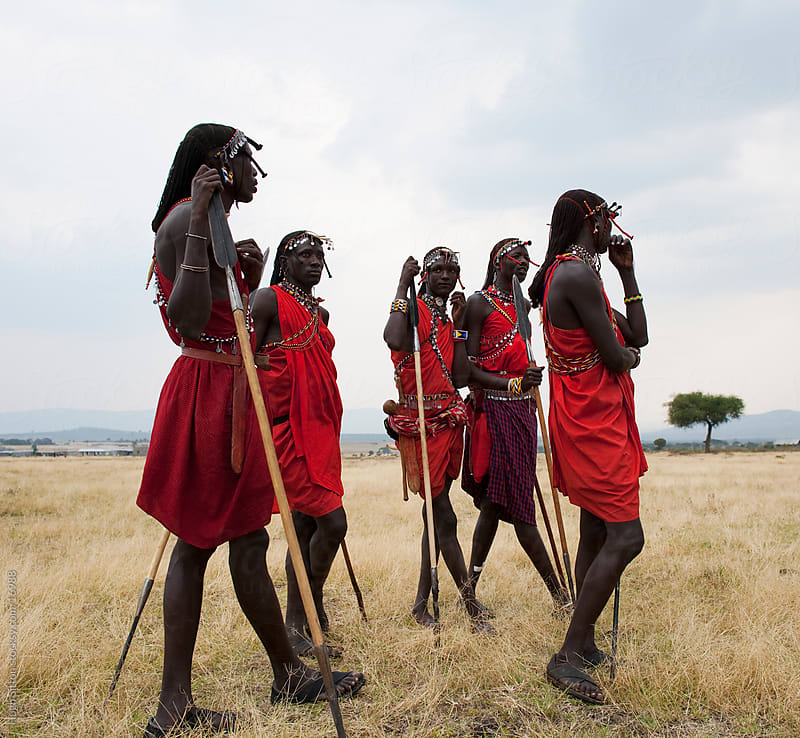 Maasai tribeman standing in the Maasai Mara. by Hugh Sitton for Stocksy United