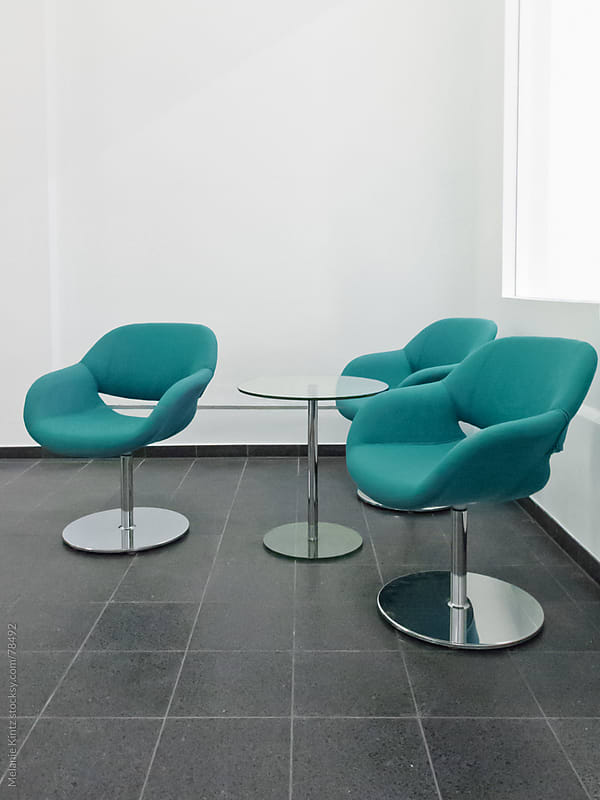 Three blue-green colored chairs in a waiting area by Melanie Kintz for Stocksy United