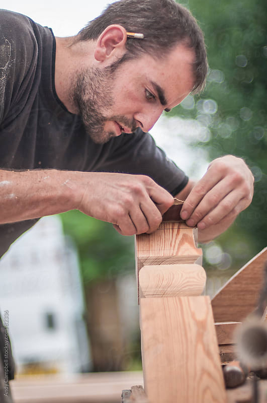 A joiner working on sanding a piece of wood by Andy Campbell for Stocksy United