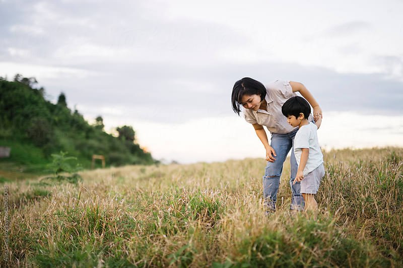 Mother and son at a grass field by Alita Ong for Stocksy United