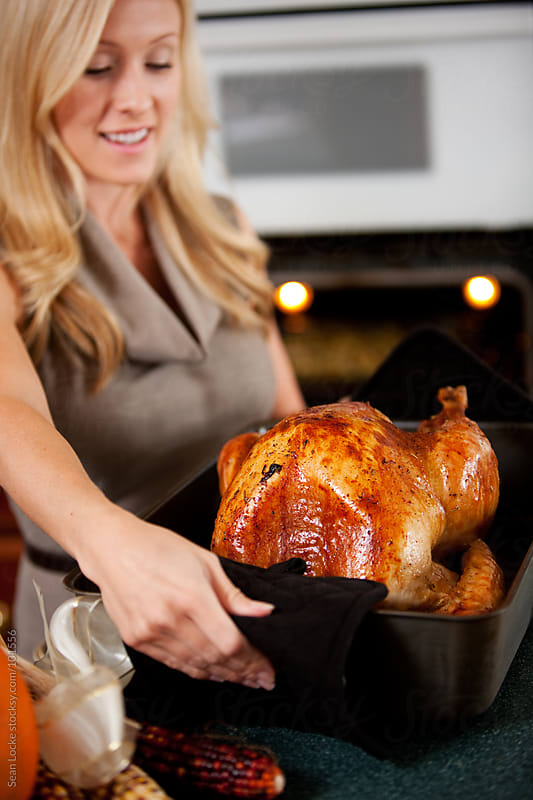 Thanksgiving: Woman Takes Finished Turkey Out of Oven by Sean Locke for Stocksy United