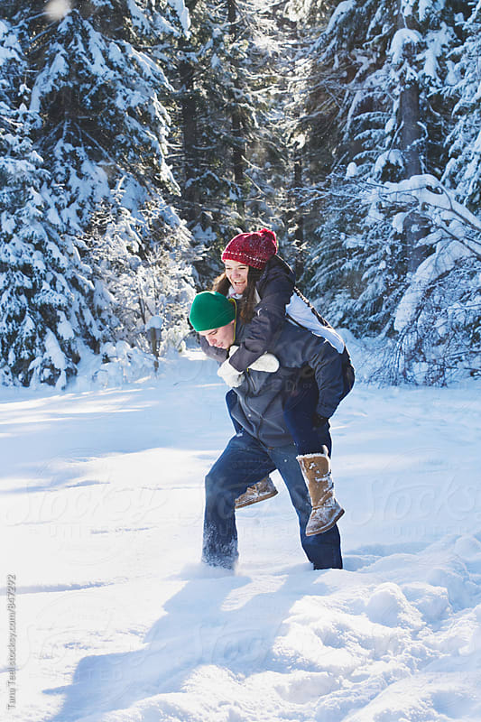 young couple playfully piggyback through snow by Tana Teel for Stocksy United