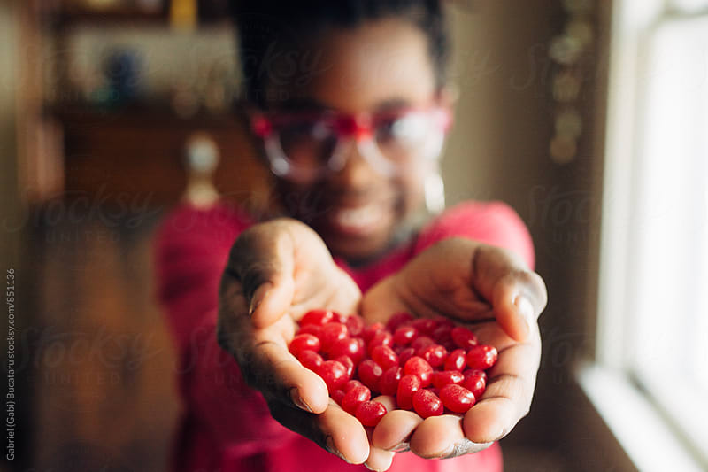 Red candy in the palm of an African American girl by Gabriel (Gabi) Bucataru for Stocksy United