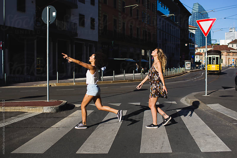Cheerful girls crossing the road at a zebra crossing by michela ravasio for Stocksy United