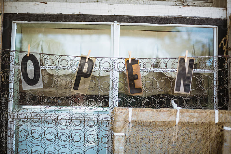open sign hanging from wooden pegs from a wire matress by Image Supply Co for Stocksy United