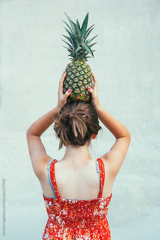 Girl in a red dress with an organic pineapple balancing on her head by Carolyn Lagattuta for Stocksy United