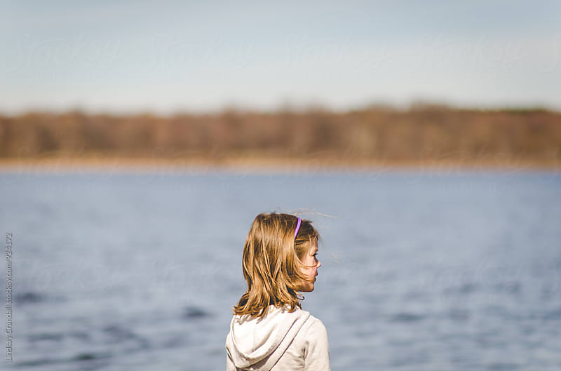 Girl standing by a body of water by Lindsay Crandall for Stocksy United