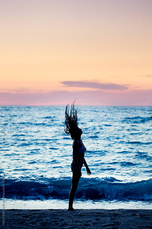 Young Woman Flicks Her Hair on the Beach at Twilight by Helen Sotiriadis for Stocksy United
