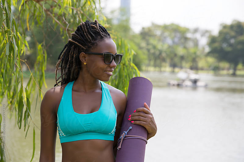 Young African woman smiling and holding her purple yoga mat by Jovo Jovanovic for Stocksy United