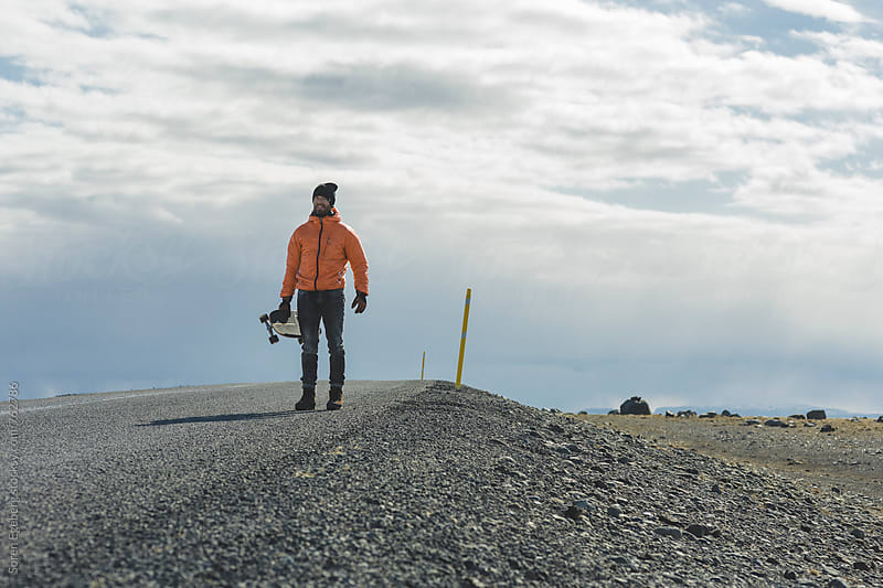 Man standing on the road with skateboard in Iceland by Soren Egeberg for Stocksy United