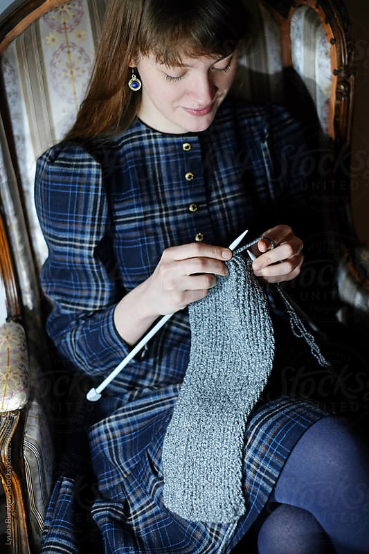 Young woman knitting a scarf at home by Lyuba Burakova for Stocksy United