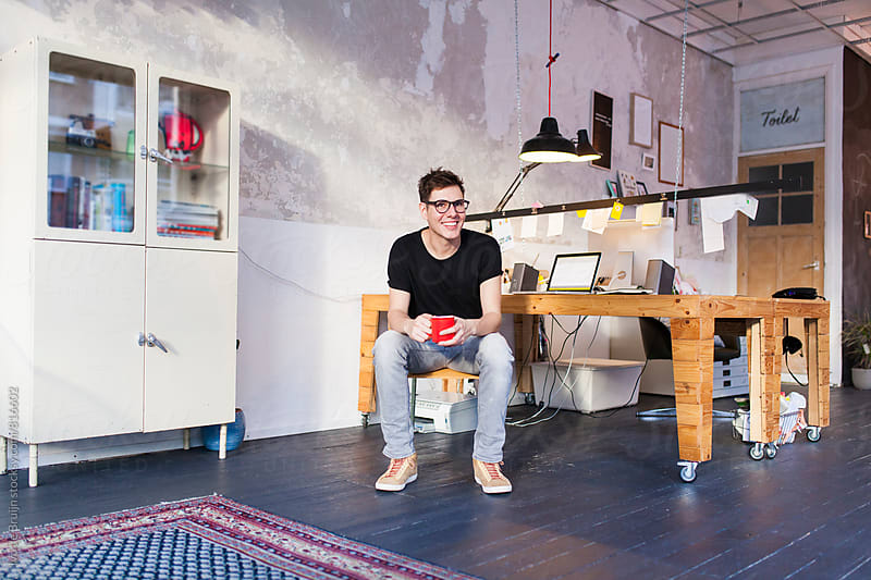 Entrepreneur or professional sittng at his desk and drinking coffee by Ivo de Bruijn for Stocksy United