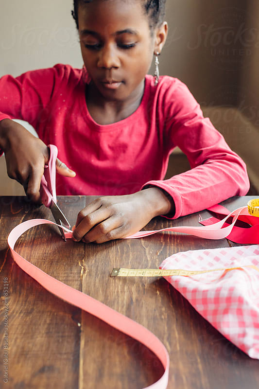 Black girl cutting a pink ribbon by Gabriel (Gabi) Bucataru for Stocksy United