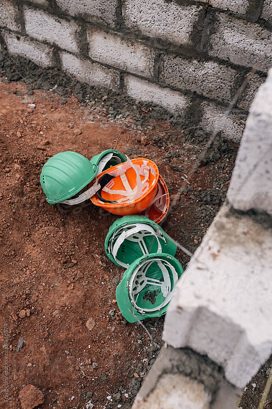 Green and orange safety hard hats on ground for charity by Trent Lanz for Stocksy United