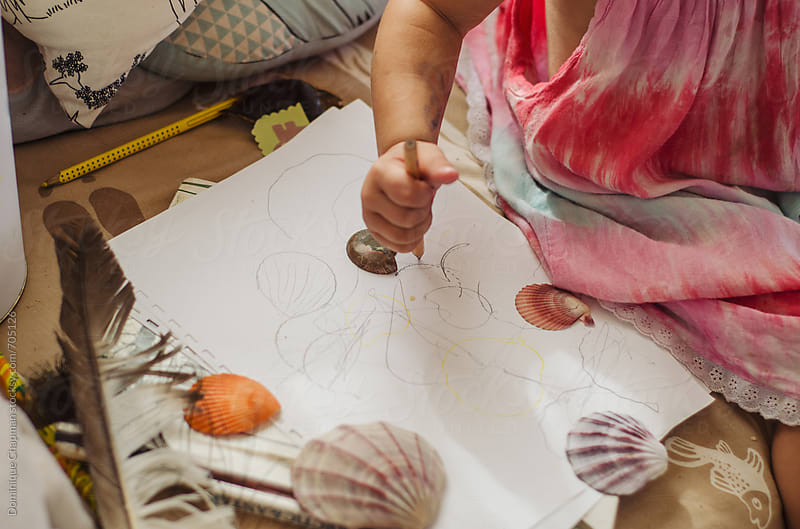 Little girl drawing shells by Dominique Chapman for Stocksy United