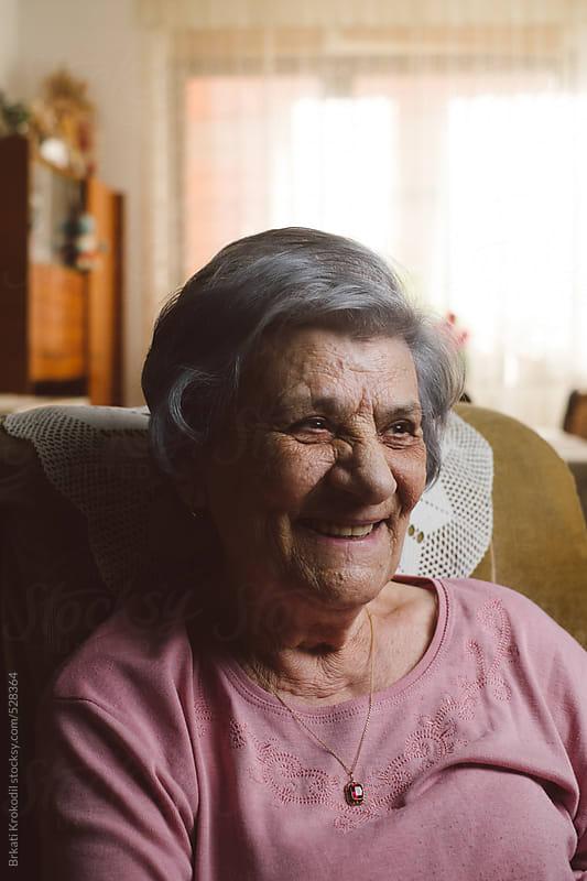 Senior woman watching tv by Brkati Krokodil for Stocksy United