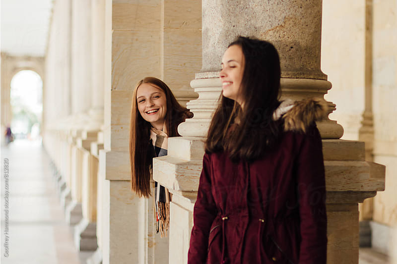 Two Girl Friends Being Playful in Colonnade by Geoffrey Hammond for Stocksy United