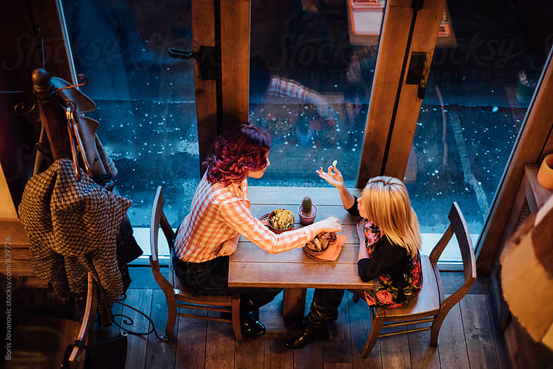 Girlfriends having a snack before dinner in the restaurant by Boris Jovanovic for Stocksy United