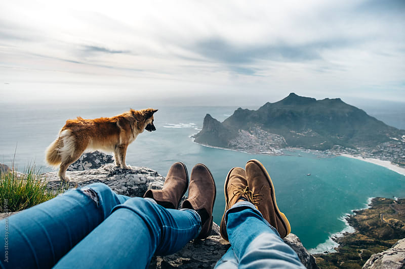 leather shoes and jeans of a relaxed hiking couple sitting at a mountain top with their dog by Micky Wiswedel for Stocksy United